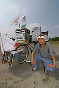 Shota Akabane (18) with his decochari customized bicycle. The bicycle has 28 lights powered by a car battery and a truck horn.