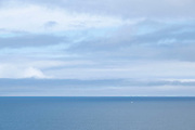 Seascape looking out over a blue sea and sky on 19th August 2021 in Mwnt, Pembrokeshire, Wales, United Kingdom. In the distance a small boat sits alone amidst the vast Atlantic Ocean.
