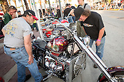 bikers inspect a custom chopper alongside Main Street during the 74th Annual Daytona Bike Week March 8, 2015 in Daytona Beach, Florida. More than 500,000 bikers and spectators gather for the week long event, the largest motorcycle rally in America.