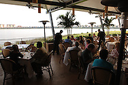 Waiters tend to dinner guests seated at an outdoor, lakefront eating area at a Seasons 52 restaurant in Orlando, Florida.  Seasons 52 is a restaurant chain owned by Darden Restaurants.