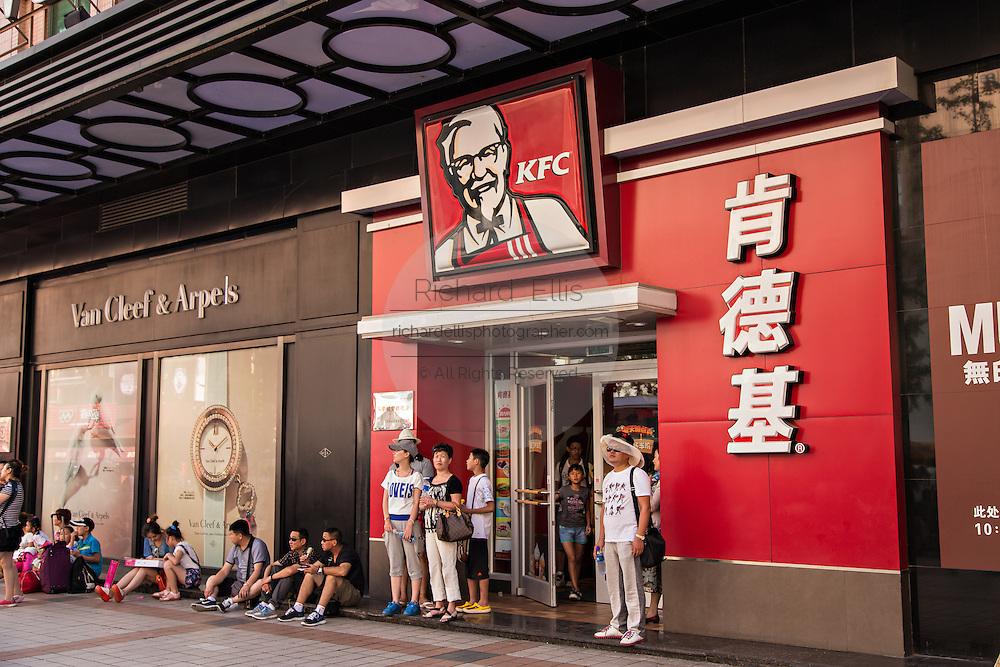People wait outside a Kentucky Fried Chicken fast food restaurant along Wangfujing Street in Beijing, China