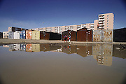 Kids play by a large puddle near the storage units that act as garages for residents of the large apartment building in the background. Ulaanbaatar, Mongolia. Material World Project.