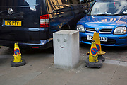 Smiling bollard and police cones at a parking bay in London, UK.