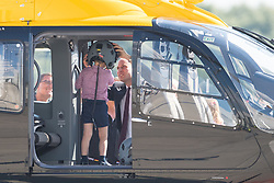 Prince George stands in a rescue helicopter as his father the Duke of Cambridge places a helmet on his head, during a visit to Airbus in Hamburg, Germany with the Duchess of Cambridge and sister Princess Charlotte.