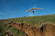 Hang glider takes off above signs of coastal soil erosion on the south side of the Isle of Wight, United Kingdom. This eroded landscape is fast approaching the coast road which links the east of the island with the west. There is currently no provision or plan to sure up the area or move the road.