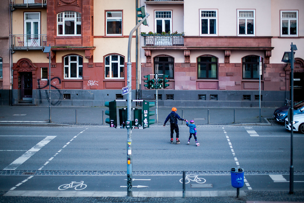 """Germany banned gatherings of more than 2 people called """"social distancing"""" because of the coronavirus. A man and his child on roller scates crossing the street at the shore of river Main in Frankfurt which is very empty on a - normally very busy - Thursday evening."""