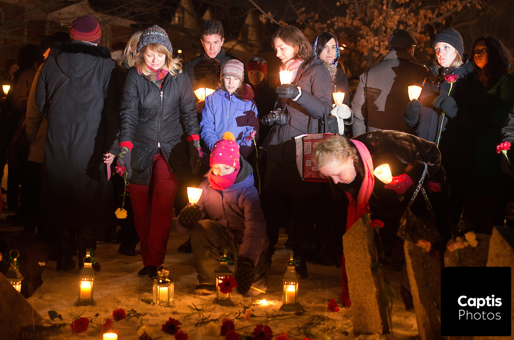 Women place roses in front of the Women's Monument during the vigil. December 6, 2014.