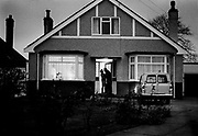 Man leaving for work at dawn, kissing his wife goodbye in the doorway of a Sidcup bungalow, in the South London suburbs. Coming and Going is a project commissioned by the Museum of London for photographer Barry Lewis in 1976 to document the transport system as it is used by passengers and commuters using public transport by trains, tubes and buses in London, UK.