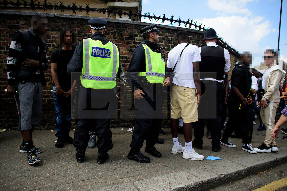 © Licensed to London News Pictures. 29/08/2016. London, UK. A group of young men being questioned by police as carnival goers enjoy day two of the Notting Hill carnival, the second largest street festival in the world after the Rio Carnival in Brazil, attracting over 1 million people to the streets of West London.  Photo credit: Ben Cawthra/LNP