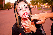 """Oct. 30, 2009 -- PHOENIX, AZ: Zombie OSLA MARTINEZ and a Zombie friend dab at blood on Osla's lips during the Zombie Walk in Phoenix Friday. About 200 people participated in the first """"Zombie Walk"""" in Phoenix, AZ, Friday night. The Zombies walked through downtown Phoenix """"attacking"""" willing victims and mixing with folks going to the theatre and downtown sports venues.  Photo by Jack Kurtz"""