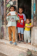 Luxor, Egypt - April 15, 2010: Three Egyptian children stand at the entrance to their home in a village several kilometers outside Luxor, Egypt. The girl is holding up her Arabic alphabet practice booklet.