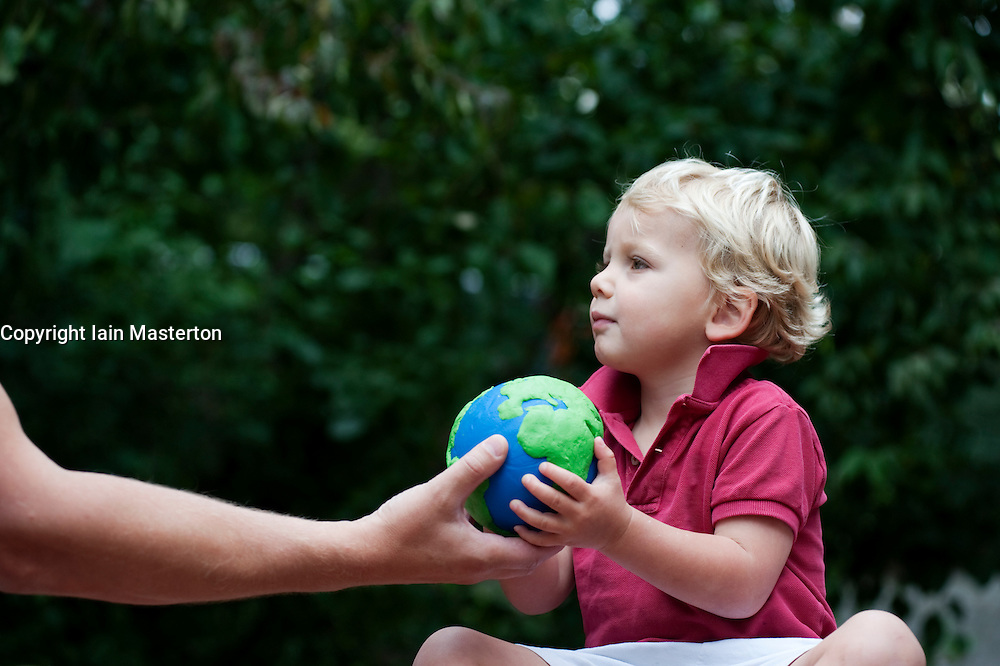 Father passing a model of planet Earth to his young son for safekeeping