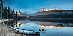 Early morning at Redfish Lake in the Sawtooth National Recreation Area in Central Idaho. The peaks of the Sawtooth Range reflecting on the water as the morning fog dissipates above.<br /> <br /> This is a 2X1 photo stitched  panorama and is a large file that can be printed 8 foot wide at 167 dpi