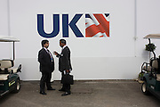 Delegates discuss business outside the UKTI Defence & Security exhibition chalet at the Farnborough Air Show.