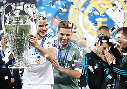 Theo Hernandez of Real Madrid and Real Madrid's French goalkeeper Luca Zidane celebrate with winner's medals and a trophy on the pitch as Real Madrid players celebrate winning the UEFA Champions League final football match between Liverpool and Real Madrid at the Olympic Stadium in Kiev, Ukraine on May 26, 2018. - Real Madrid defeated Liverpool 3-1. Photo by Andriy Yurchak / Sportida
