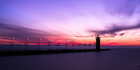 A long exposure of the post sunset lit clouds streaking over the South Haven, Mi lighthouse
