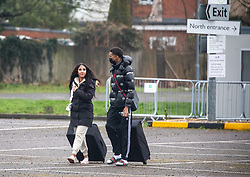© Licensed to London News Pictures. 15/02/2021. London, UK. Two members of the public with suitcases walk past a Covid-19 test centre in the car park of the Radisson Hotel a quarantine hotel near Heathrow this morning. From today, (Monday 15 February 2021) anyone arriving from a red-list destination must quarantine at a designated hotel and pay a hotel fee of £1,750 for a 10 day quarantine period. Photo credit: Alex Lentati/LNP