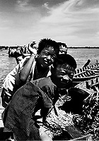 Vietnamese boys laughing and playing on a river dock in Mekong Delta.
