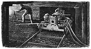 Hydraulic coal cutting machine, named 'The Iron Man', in position on rail track undergground in a coal seam. Made by Carrett, Marshall & Co., and shown at the Paris International Exposition of 1867. Wood engraving.