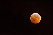 Full moon colored orange while passing into the earth's shadow during a lunar eclipse