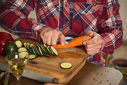 Midsection of a man peeling carrot on chopping board, Munich, Bavaria, Germany