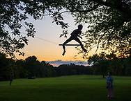 """Old Westbury, New York, U.S., September 1, 2019. """"Athlete 1 - Over the Hurdle"""" seen silhouetted by sky at upper right, is one of 33 outdoor sculptures by Jerzy Kedziora (Jotka), b. 1947 in Poland, and his Balance in Nature art is on view at historic Old Westbury Gardens in Long Island, until October 20, 2019. Seen at dusk, the life-size, bronze resin balancing sculpture, is balanced on wire suspended from trees. Athlete III - Deep Plunge is seen dimly at lower left ground."""