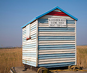 Old seaside beach hut with notice sign for boat trips at Slaughden, Aldeburgh, Suffolk, England