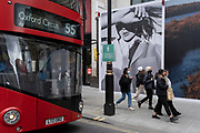 On the day that the UK government eased Covid restrictions to allow non-essential businesses such as shops, pubs, bars, gyms and hairdressers to re-open, a bus queues alongside shoppers on Oxford Street and a large fashion retail ad, on 12th April 2021, in London, England.