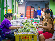 19 OCTOBER 2012 - BANGKOK, THAILAND:  Guava vendors sort fruit in their booth in the Bangkok Flower Market. The Bangkok Flower Market (Pak Klong Talad) is the biggest wholesale and retail fresh flower market in Bangkok.  The market is busiest between 3:30AM and 6AM. Thais grow and use a lot of flowers. Some, like marigolds and lotus, are used for religious purposes. Others are purely ornamental.          PHOTO BY JACK KURTZ
