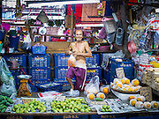 "05 APRIL 2014 - BANGKOK, THAILAND:   A fruit vendor in Khlong Toey Market in Bangkok. Khlong Toey (also called Khlong Toei) Market is one of the largest ""wet markets"" in Thailand. The market is located in the midst of one of Bangkok's largest slum areas and close to the city's original deep water port. Thousands of people live in the neighboring slum area. Thousands more shop in the sprawling market for fresh fruits and vegetables as well meat, fish and poultry.     PHOTO BY JACK KURTZ"