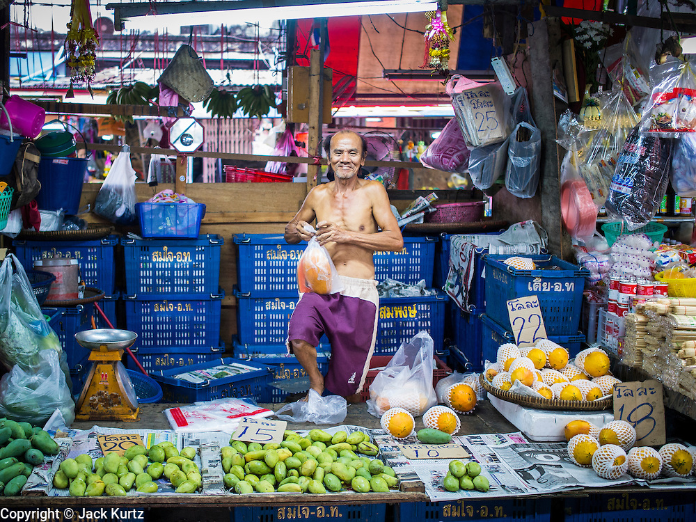 """05 APRIL 2014 - BANGKOK, THAILAND:   A fruit vendor in Khlong Toey Market in Bangkok. Khlong Toey (also called Khlong Toei) Market is one of the largest """"wet markets"""" in Thailand. The market is located in the midst of one of Bangkok's largest slum areas and close to the city's original deep water port. Thousands of people live in the neighboring slum area. Thousands more shop in the sprawling market for fresh fruits and vegetables as well meat, fish and poultry.     PHOTO BY JACK KURTZ"""