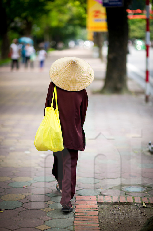 An old buddhist nun in a brown outfit is walking alone on the street. She is carrying a yellow bag on her thin shoulder. Hanoi, Vietnam, Asia.