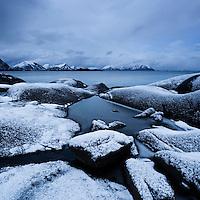 Snow covered rocky coastline at Stamsund, Vestvågøy, Lofoten islands, Norway