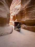 "Carriage in the siq slot canyon exiting from the Treasury, a facade carved out of stone by the Nabataeans. Currently one of the ""Seven Wonders of the World"""
