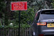 A car passes the signpost at the junction of the South Circular A205 and College Road in Dulwich Village, warning motorists of the restrictions preventing traffic from passing through at morning and afternoon rush-hour times in the borough of Southwark, on 15th June 2021, in London, England.