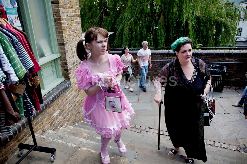 Mother Louise Irwin-Ryan with her daughter Georgia (11, wearing a pink Lolita dress) spending a day out together in Camden Town, North London. Louise who struggles to walk up the steps is on various benefits to help support her family income, and housing, although recent government changes to benefits may affect her family drastically, possibly meaning they may have to move out of London. Louise Ryan was born on the Wirral peninsula in 1970.  She moved to London with her family in 1980.  Having lived in both Manchester and Ireland, she now lives permanently in North London with her husband and two children. Through the years Louise has battled to recover from a serious motorcycle accident in 1992 and has recently been diagnosed with Bipolar Affective Disorder. (Photo by Mike Kemp/For The Washington Post)