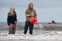 Claudia Zeiske and her daughter Rachel Zeiske-May arrive in Portobello to complete their walking art work, POSTCARDS FROM THE SHIFTING SHORE. The piece involved a Slow Marathon along coastlines on opposite sides of the world to generate debate on rising sea levels. The 42km walk took place simultanousely at two different locations (Firth of Forth and Cape of Good Hope, South Africa). Both Claudia and  her South African counterpart, Jaak Coetzer. walked with a red watering can, pouring water into the sea and taking water out of the sea. Each artist was accompnied by one of their adult children and en route they discussed the issues surrounding climate change,rising sea waters and what it means for them and their children's future.<br /> © Jon Davey/ EEm