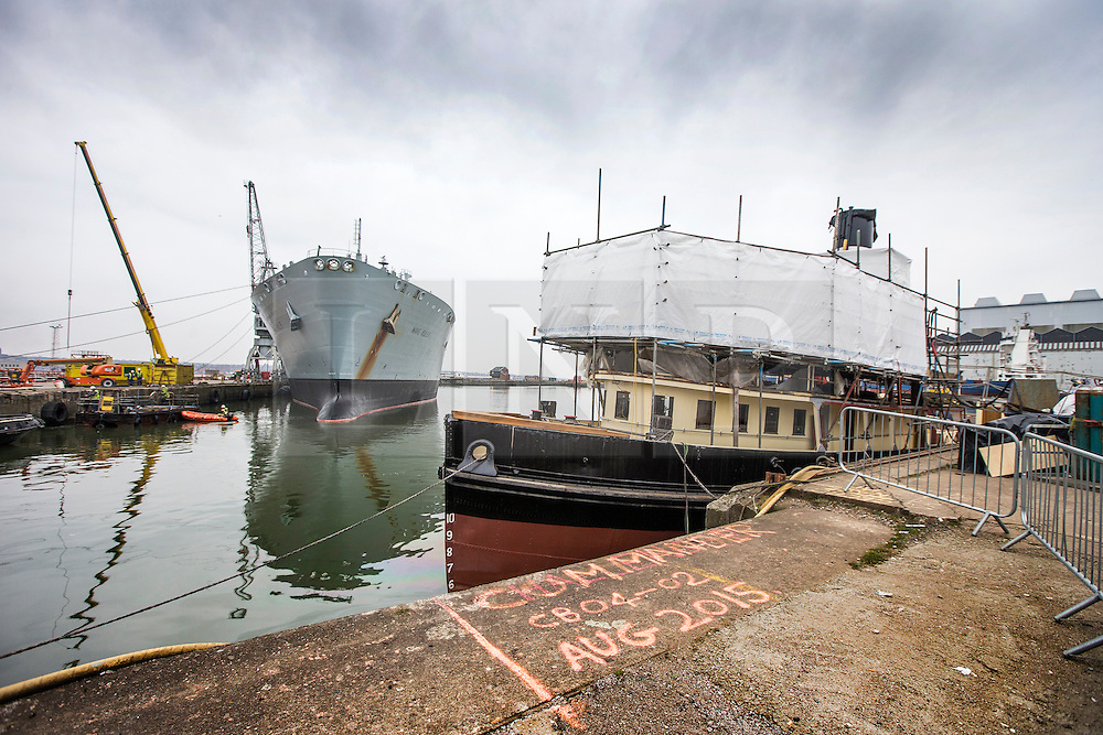 """© Licensed to London News Pictures. 04/05/2016. Birkenhead UK. Picture shows restoration work being carried out on the Daniel Adamson at Camel Laird docks in the shadow of RFA Wave Ruler. The Daniel Adamson steam boat has been bought back to operational service after a £5M restoration. The coal fired steam tug is the last surviving steam powered tug built on the Mersey and is believed to be the oldest operational Mersey built ship in the world. The """"Danny"""" (originally named the Ralph Brocklebank) was built at Camel Laird ship yard in Birkenhead & launched in 1903. She worked the canal's & carried passengers across the Mersey & during WW1 had a stint working for the Royal Navy in Liverpool. The """"Danny"""" was refitted in the 30's in an art deco style. Withdrawn from service in 1984 by 2014 she was due for scrapping until Mersey tug skipper Dan Cross bought her for £1 and the campaign to save her was underway. Photo credit: Andrew McCaren/LNP ** More information available here http://tinyurl.com/jsucxaq **"""