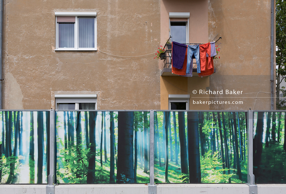 A hoarding featuring forestry and the washing hanging on an apartment balcony in the Slovenian capital, Ljubljana, on 28th June 2018, in Ljubljana, Slovenia.