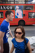 As passers-by walk along a London street, they have behind them, a red London bus advertising the international clothing businesses mango.com. The man and lady are out of focus and wear the same blue coloured tops while the model in the poster wears a pink dress, leaning against a wall. The ad is above the wheel of the bus.