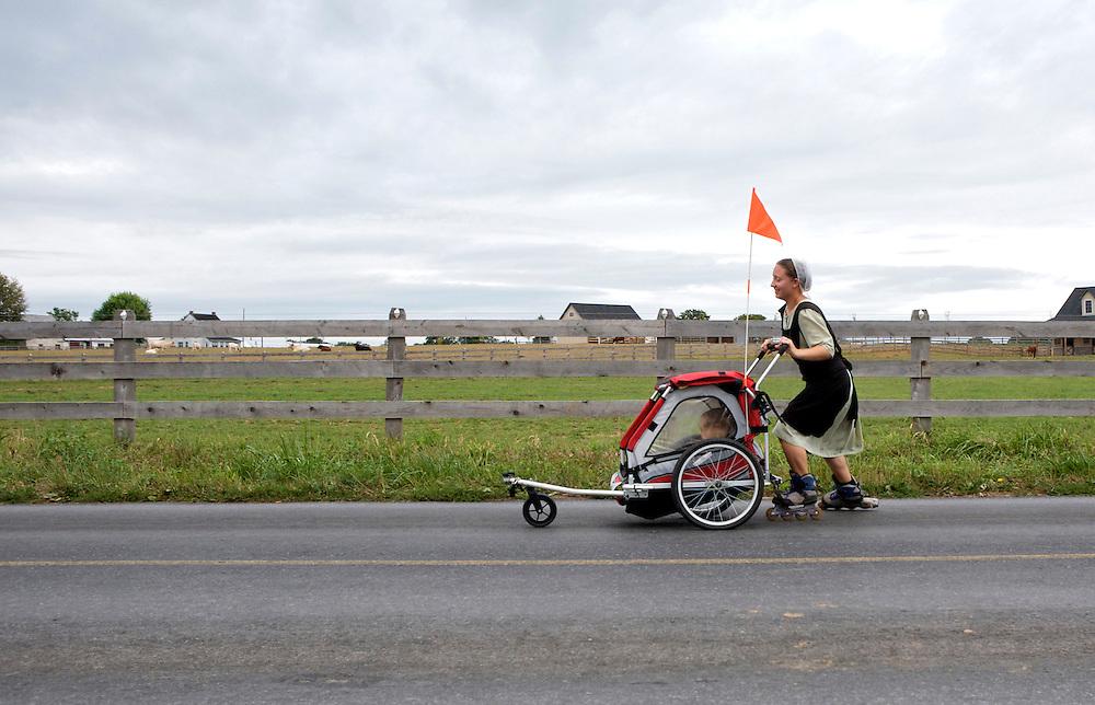UNITED STATES-LANCASTER COUNTY-Amish. Mother on rollerblades. VERENIGDE STATEN-LANCASTER COUNTY-Een jonge moeder uit de Amish gemeenschap duwt een wagentje voort met daarin haar kinderen. De Amish moeten voldoen aan strenge regels. Zo is zelf autorijden en fietsen verboden, maar jezelf verplaatsen op een step of op rolschaatsen is wel toegestaan en populair onder de wat modernere Amish.  ANP PHOTO COPYRIGHT GERRIT DE HEUS