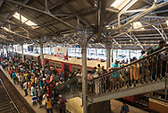 A crowd of people navigate the platform and staircase at Fort railway station, a major hub for Sri Lanka Railways in Colombo, Sri Lanka.
