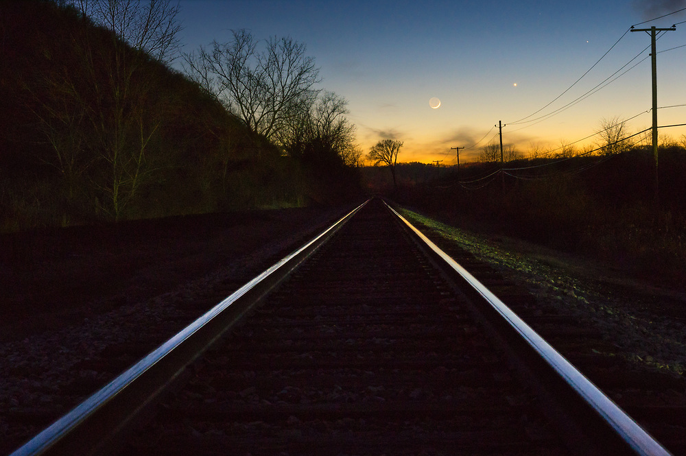 Mercury, Venus, and a waxing crescent moon line the evening sky above the setting sun and a set of railroad tracks.