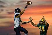 """MMU's Mason Combs (80) passes the ball over BFA""""s Adam Forbes (24) during the football game between the Mount Mansfield Cougars and the BFA St. Albans Bobwhites at BFA High School on Friday night September 7, 2018 in St. Albans. (BRIAN JENKINS/for the FRESS PRESS)"""