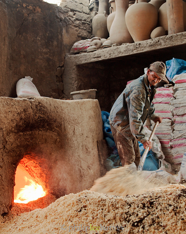 A man fuelling a kiln, used for firing pottery, with woodchip at an artisanal workshop in Fes, Morocco