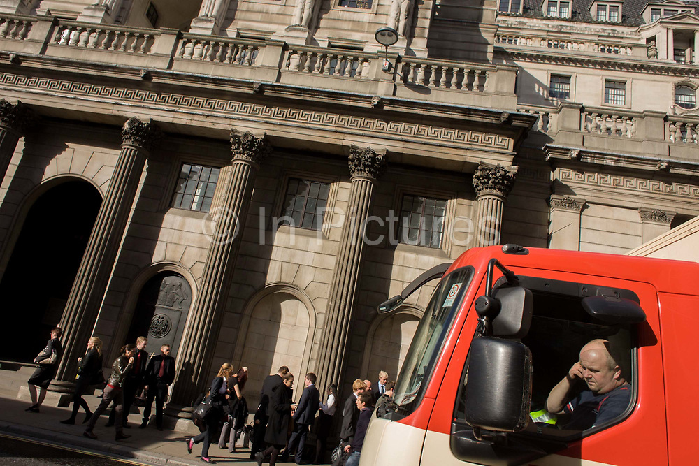 """Truck passenger and incidental people outside the Bank of England in the City of London, England UK. While stopped at a red light, the lorry is passing the pillars and architecture of Britain's main bank. The Bank of England is the central bank of the United Kingdom. Sometimes known as the """"Old Lady"""" of Threadneedle Street, the Bank was founded in 1694, nationalised on 1 March 1946, and in 1997 gained operational independence to set monetary policy."""