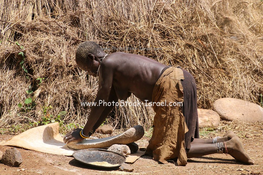 Woman of the Mursi tribe milling grain to flour. Photographed in Debub Omo Zone, Ethiopia. Close to the Sudanese border.