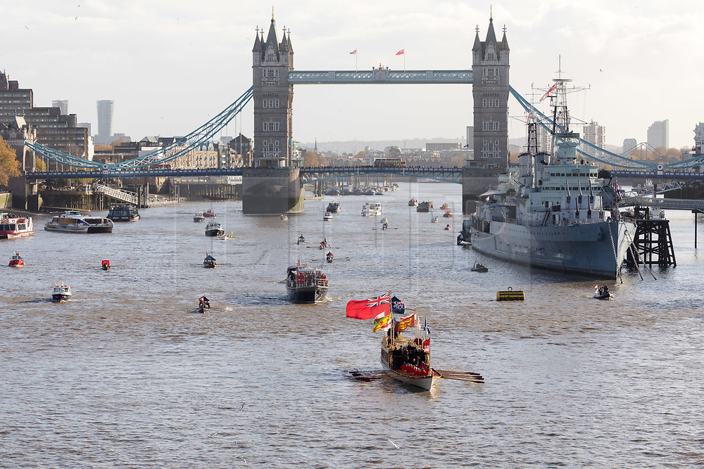 © Licensed to London News Pictures. 11/11/2018. London, UK.  A flotilla of boats including the Royal barge, QRB Gloriana, the Havengore and traditional boats travel up the River Thames in front of Tower Bridge towards the Houses of Parliament in Westminster for a remembrance service, led by the Havengore, as part of Armistice Day centenary events taking place in central London. Big Ben will strike at 11am to mark the start of the two minutes silence and the Havengore will sound her horn to signify the end of the two minutes silence in central London.  Photo credit: Vickie Flores/LNP