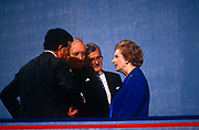 Ex British Prime Minister Margaret Thatcher speaks with ex colleagues on podium during John Major's 1991 Tory party conference. A year after her colleagues deposed her, forcing her to resign from her 11 year premiership, she chats on stage after her speech with former cabinet ministers John Wakeham, Willie Whitelaw and Kenneth Baker. Thatcher has been lending her support to her replacement, the former Chancellor and Foreign Secretary, but the otherwise unknown John Major who governed until 1997.