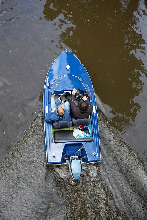 Twee mannen varen in een speedboot door de Oudegracht in Utrecht.<br /> <br /> Two man are boating in a speed boat at the canals in Utrecht.